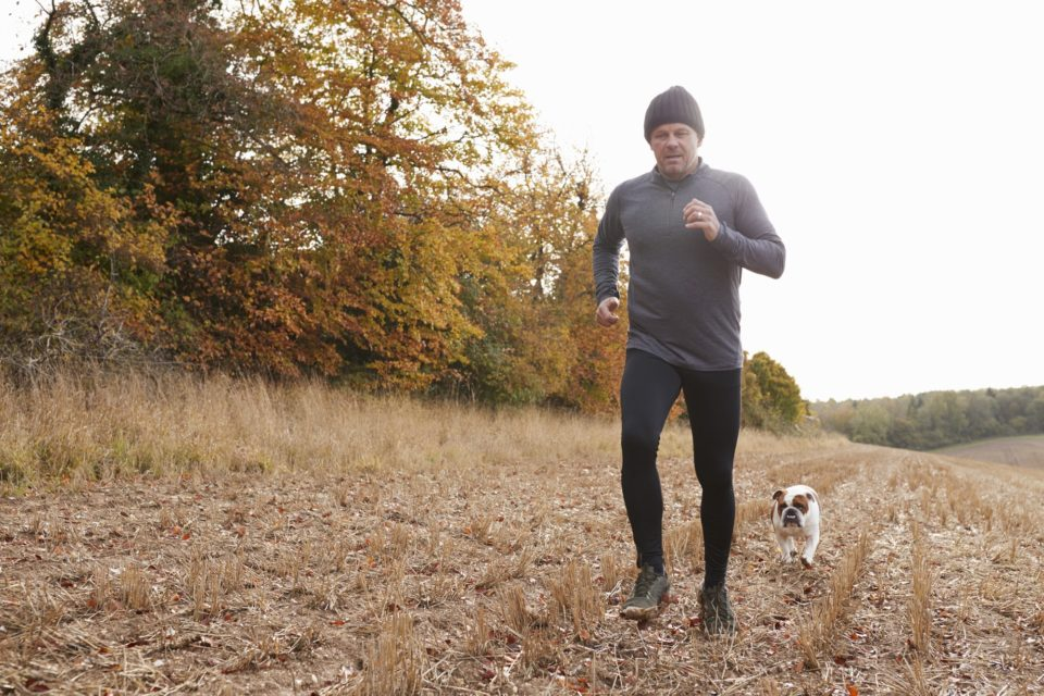Mature Man Running Around Autumn Field With Pet Bulldog