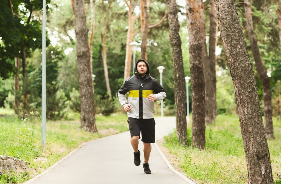 Young sporty man jogging in autumn park