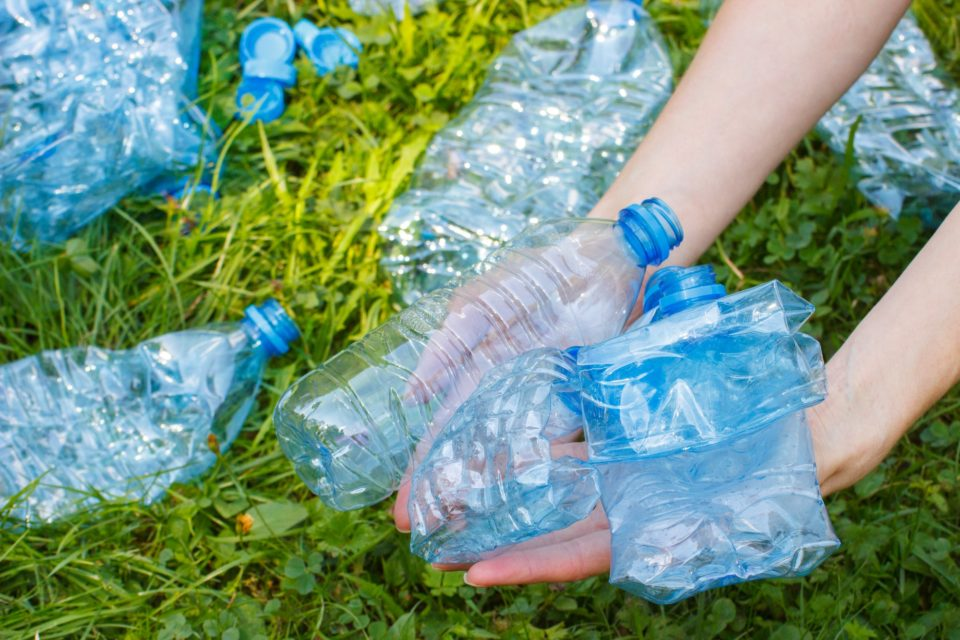 Bottles of mineral water in hand of woman, littering of environment