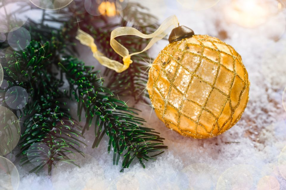 Golden Christmas ball on snow near branches of fir tree. Festive background with copy space