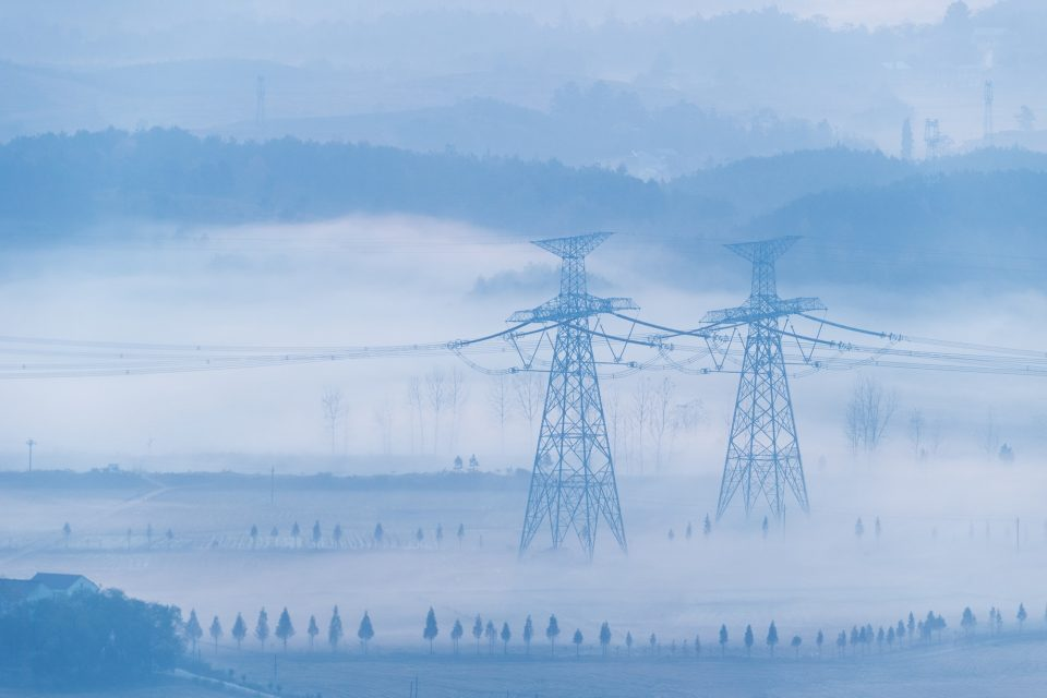 power transmission towers in the morning fog