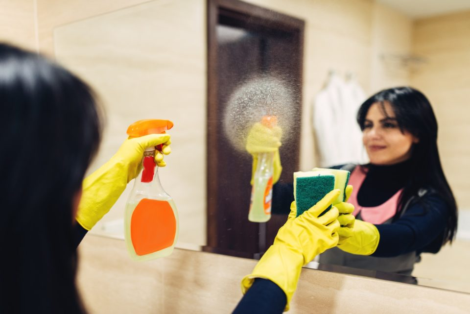 Housemaid cleans the mirror with a cleaning spray