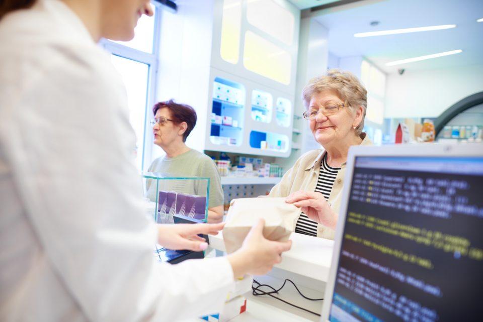 Pharmacist handing medication to customer