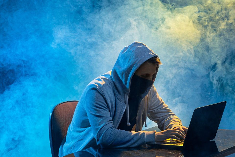 Hooded computer hacker stealing information with laptop