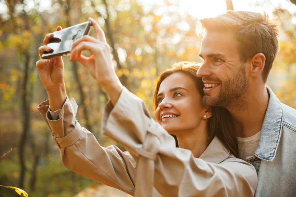 Beautiful young couple in love using mobile phone