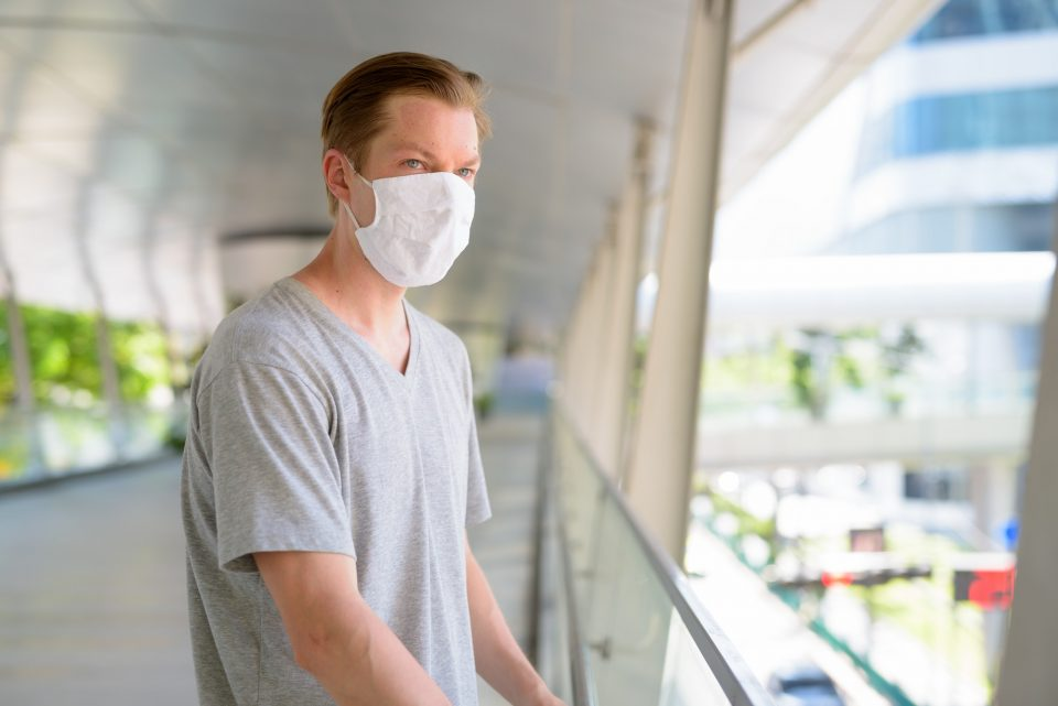 Young man looking at view of the city with mask for protection from corona virus outbreak