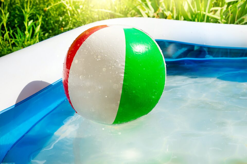 Beach ball floating in swimming pool in the yard.