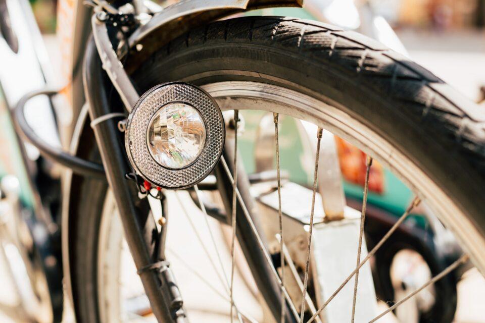 Close Up Of Bike Headlight And Wheel Of Bicycle On Street. Bike