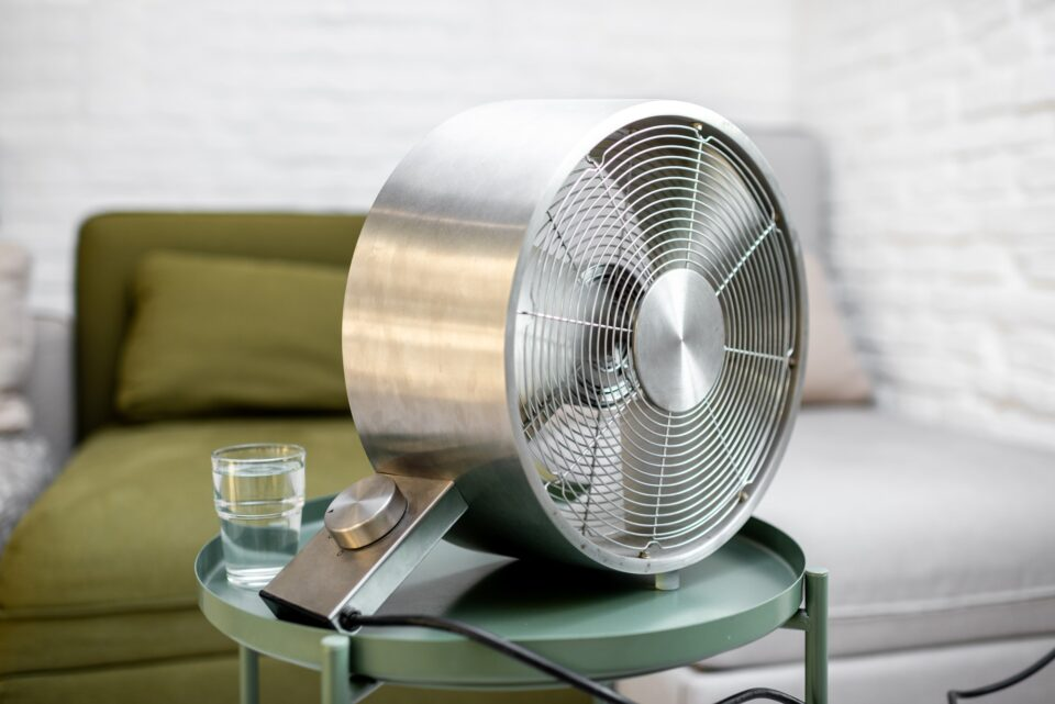 Fan with a glass of water on the table at home