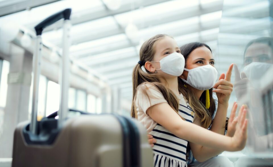 Mother with daughter going on holiday, wearing face masks at the airport