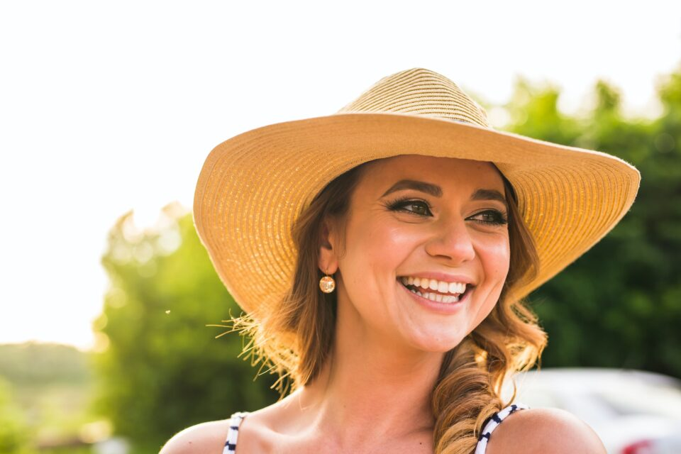 Portrait of pretty cheerful woman wearing straw hat in sunny warm weather day.