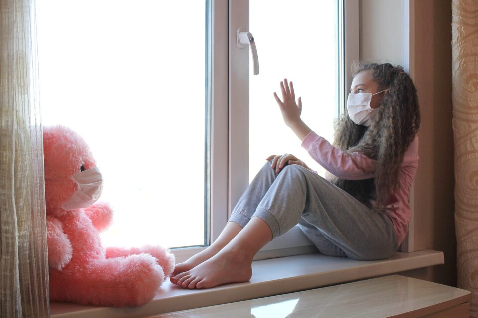 A girl in a medical mask sits on the windowsill and touches the window with her hand