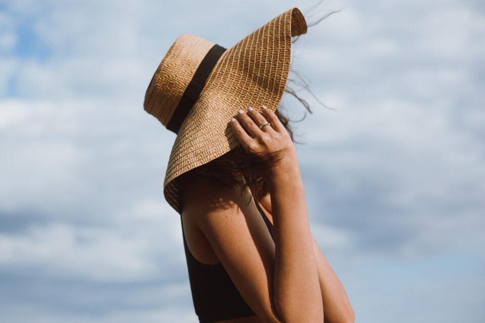 Tanned girl holding hat and posing on background of blue sky in hot summer day