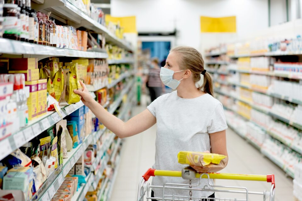 masked woman is shopping at the supermarket
