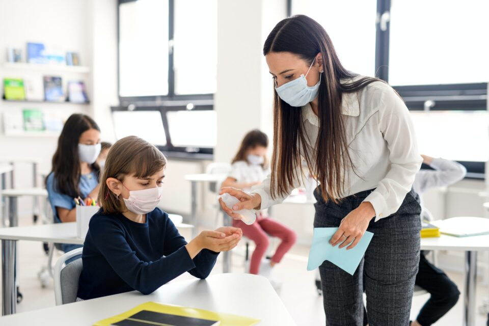 Teacher, children with face mask at school after covid-19 quarantine and lockdown