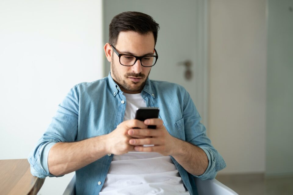 Young smiling man surfing the net and text messaging with mobile phone