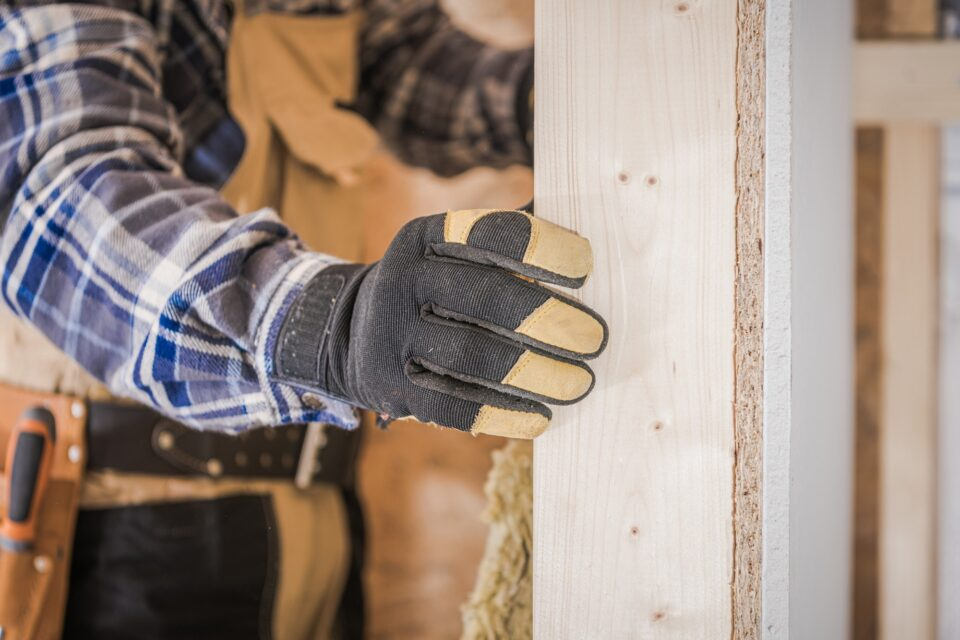 Close Up Of Male Worker Adding Insulation To Walls During House Renovation.