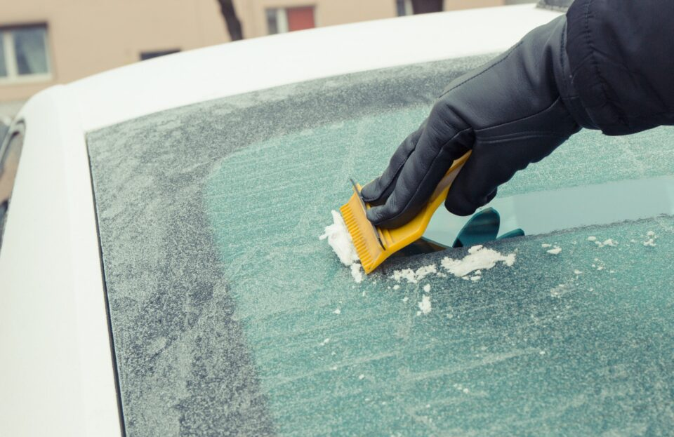 Hand holding yellow scraper and removing ice or snow from car window