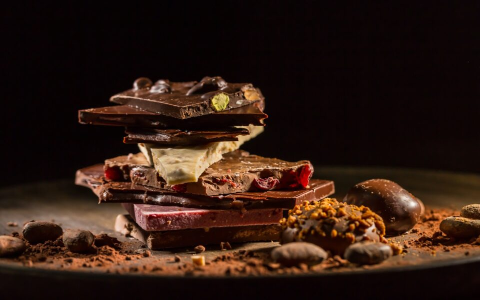 Stack of assorted chocolate with cocoa and cocoa beans on black background