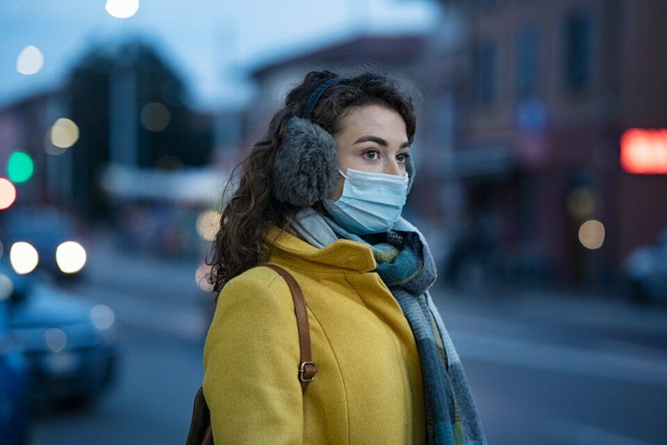Winter woman wearing mask in city street
