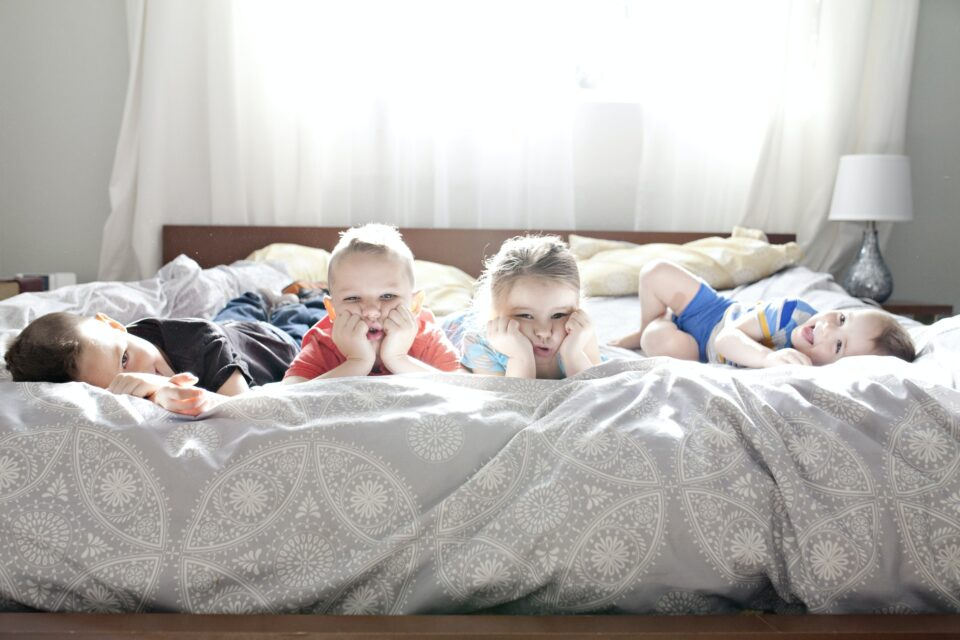 Four kids posing for a photo on a giant bed. They all look unhappy.