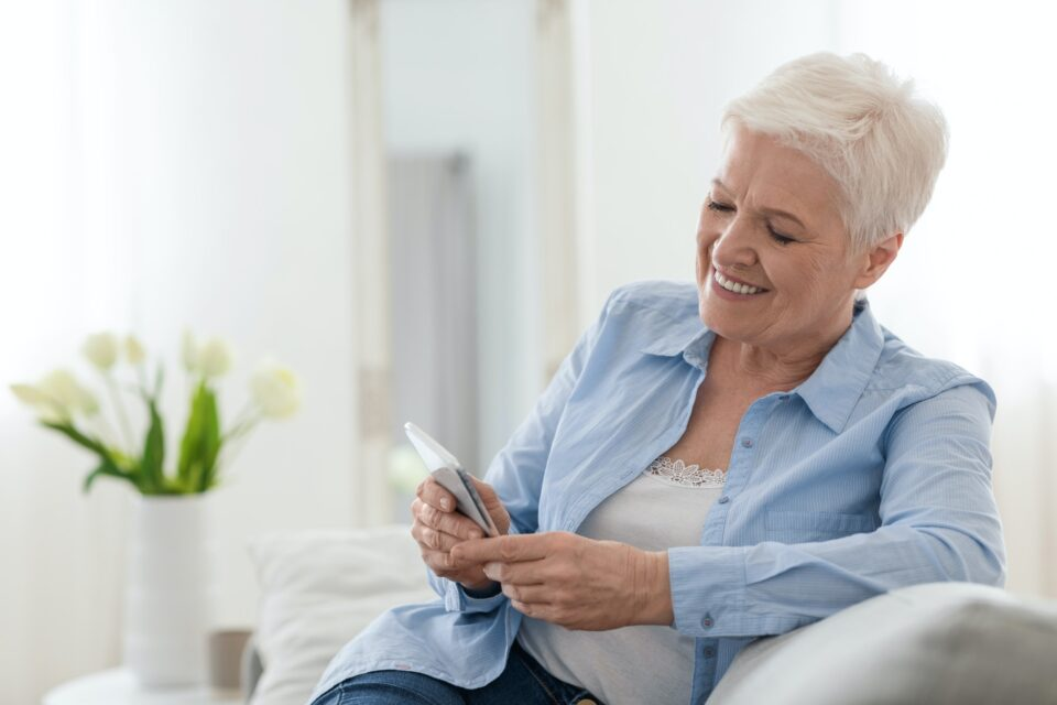 Happy elderly lady using mobile phone while relaxing on couch at home