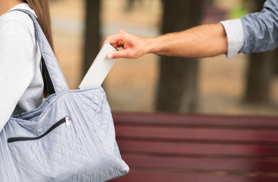 Thief Pickpocketing Smartphone From Lady's Bag Outdoor, Closeup, Cropped