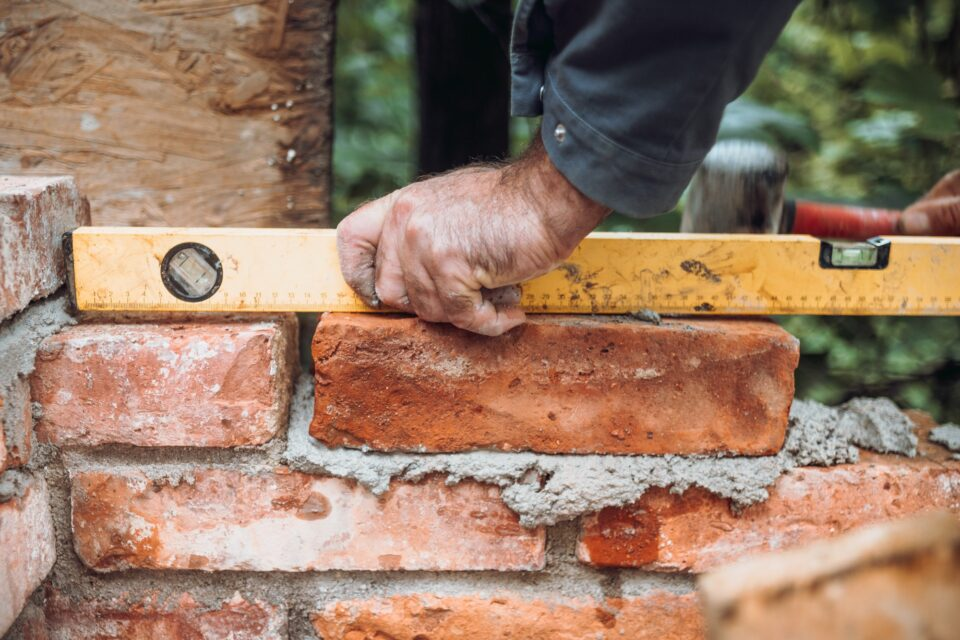 closeup of construction worker installing bricks using level, building house