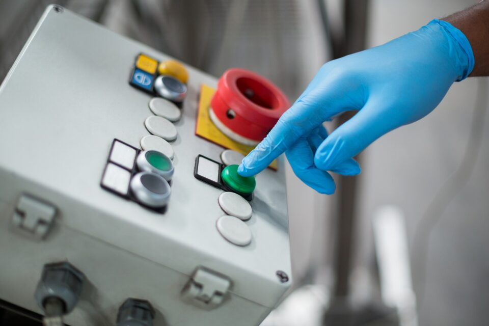 Factory engineer pressing button in bottle factory