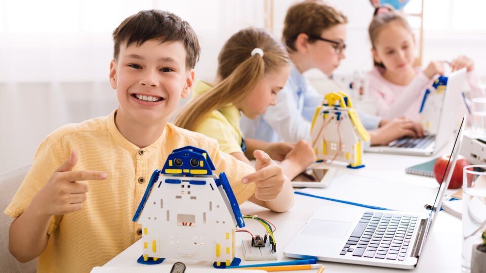 Happy schoolboy showing his robot, pointing with finger