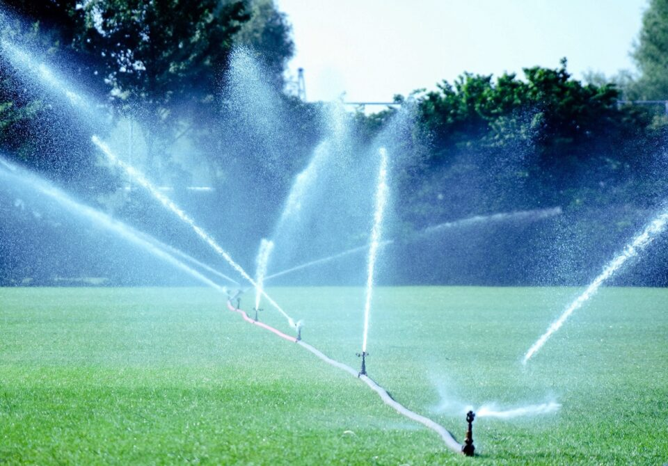 Spraying water on the football field in the hot and dry summer.
