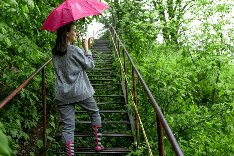 A girl walks in the forest with an umbrella in rainy weather.