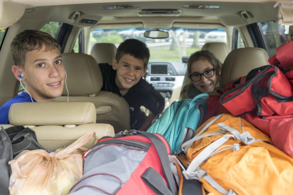 Siblings packed into the family car for a road trip