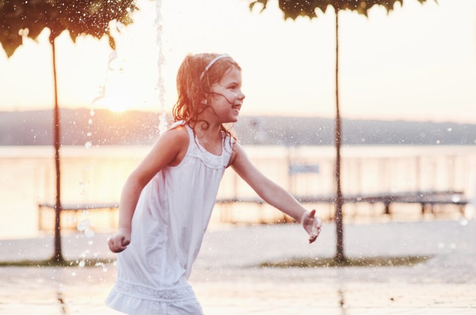 Smiling and happy. Young girl play in the fountain at the summer heat and lake and woods background