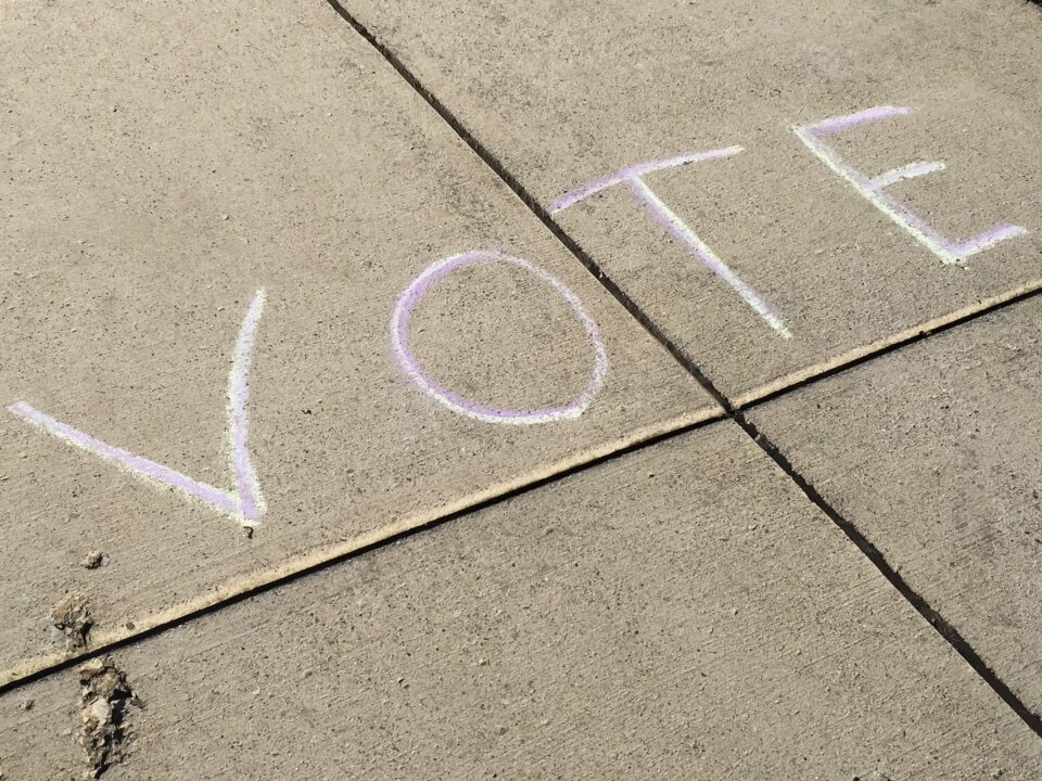 The word VOTE written with sidewalk chalk on pavement to remind people to go vote